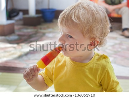 Little toddler boy eating colorful ice cream in summer