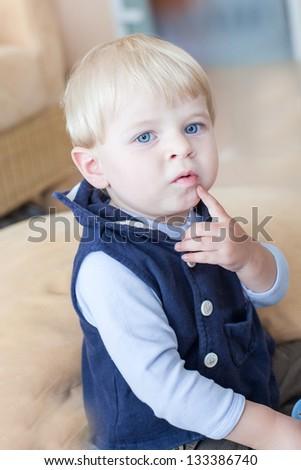 Little toddler boy eating fresh blueberry indoor - stock photo