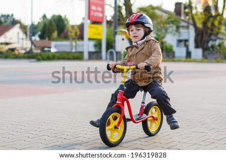 Little toddler boy having fun and riding his bike  in the city