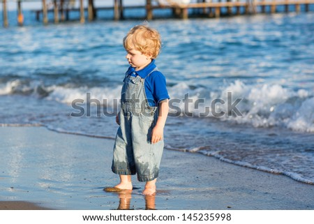 Little toddler boy having fun on the beach in summer, vacations