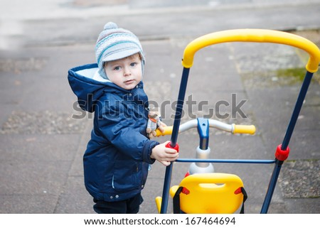 Little toddler boy in autumn park on bicycle . - stock photo