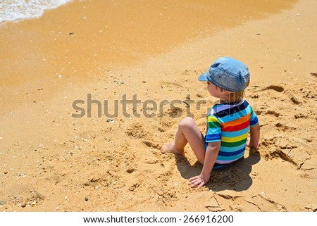 Little toddler boy in striped t-shirt and denim cap sitting back on sandy beach - stock photo