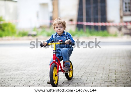 Little toddler boy learning to ride on his first bike - stock photo