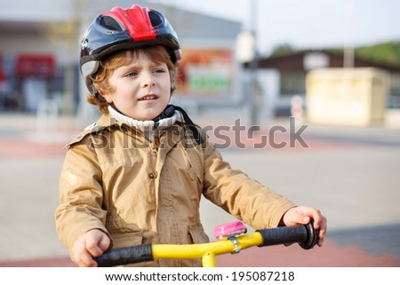 Little toddler boy learning to ride on his first bike  in the city - stock photo