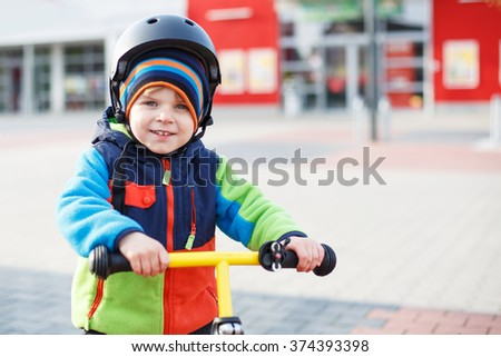 Little toddler boy learning to ride on his first bike  in the city. Kid boy in helmet having fun with active leisure. - stock photo