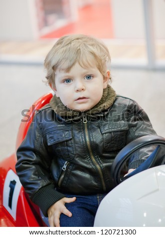 Little toddler boy on car in shopping mall