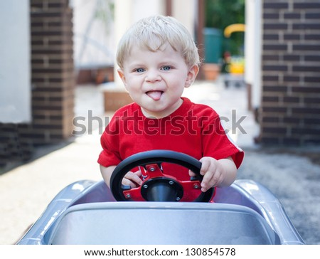 Little toddler boy playing with big toy car in summer garden - stock photo