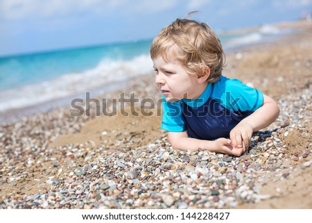 Little toddler boy playing with sand and stones on the beach in summer