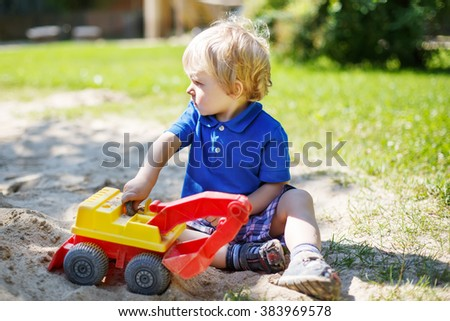 Little toddler boy playing with sand and toy on playground in summer - stock photo