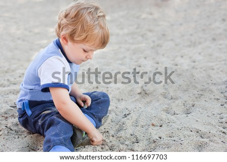 Little toddler boy playing with sand on playground in summer
