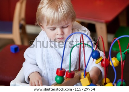 Little toddler boy playing with toy in cafe - stock photo