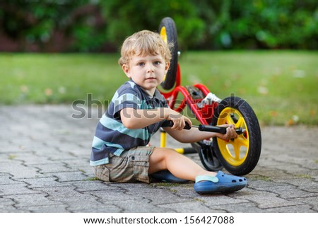 Little toddler boy repairing his first bike - stock photo