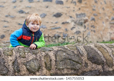 Little toddler boy sitting on castle wall outdoors in autumn
