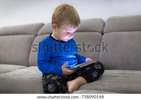 Little toddler boy watch cartoons on the tablet