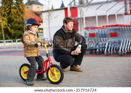 Little toddler boy with bicycle and his father in the city. Cute kid boy in safety helmet having fun outdoors in spring. Family of two together - stock photo