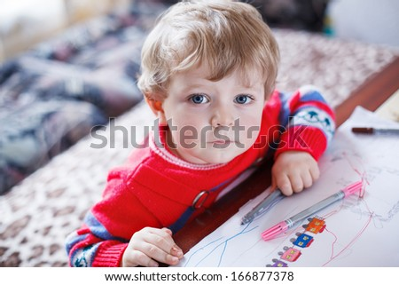 Little toddler boy with blue eyes drawing indoor with colorful pens - stock photo
