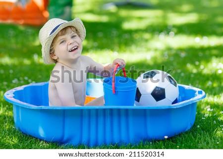 Little toddler child in hat having fun with splashing water in summer garden pool - stock photo