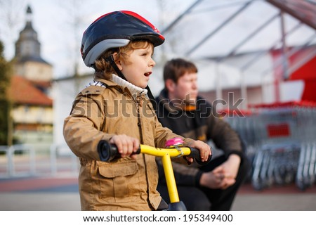 Little toddler child with bicycle and his father in the city. Happy family of two - stock photo