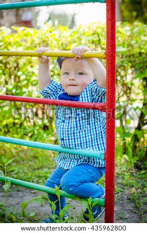 Little toddler climbing the ladder having fun at playground in summer. Cute young boy, kid or child playing outdoors on playground. Stylish little baby boy in fashionable bow-tie is clapping hands. - stock photo