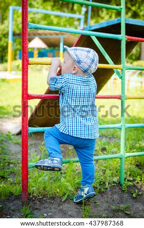 Little toddler climbing the ladder having fun at playground in summer. Cute young boy, kid or child playing outdoors on playground. Stylish little baby boy in blue shirt, pants and hat. Summer time. - stock photo