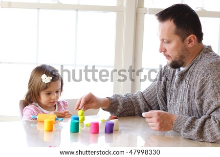 Little toddler girl and father creating toys from playdough