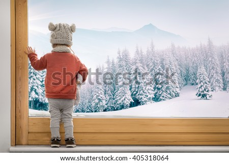 little toddler girl boy looking through window at a snowy landscape forest winter dreamy - stock photo