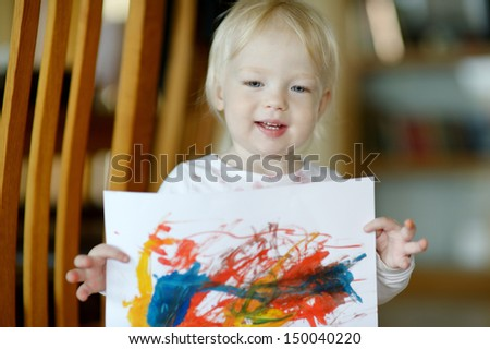 Little toddler girl displaying her picture proudly - stock photo