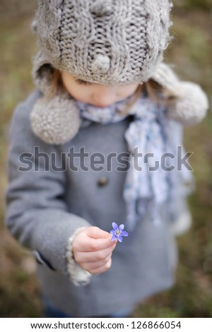 Little toddler girl holding a first flower of spring - stock photo