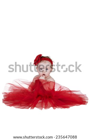 little toddler girl in a red netting dress with a red flower in her hair isolated on a white background in studio - stock photo