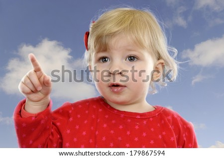 Little toddler girl in red outdoors against a blue sky with clouds