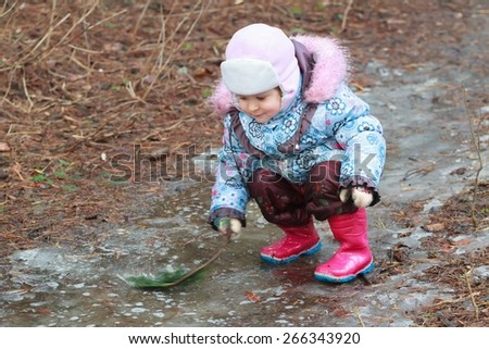 Little toddler girl in warm clothing is exploring icy puddle with pine branch - stock photo