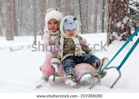 Little toddler girl in warm coat and knitted hat and happy toddler boy sitting on the sledge in the winter forest, outdoor portrait - stock photo