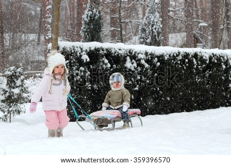 Little toddler girl in warm coat and knitted hat pulls her happy toddler brother sitting on the sledge in the winter forest, outdoor portrait - stock photo