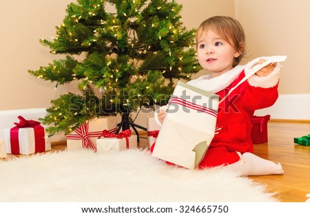 Little toddler girl opening presents under the Christmas tree - stock photo