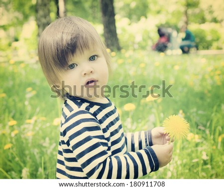 Little toddler girl outdoor and holding yellow flower dandelion retro toned - stock photo