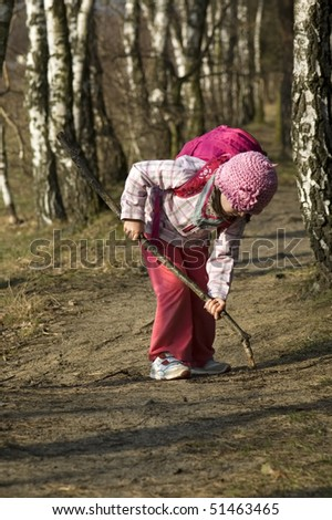 Little toddler girl playing in a forest - stock photo