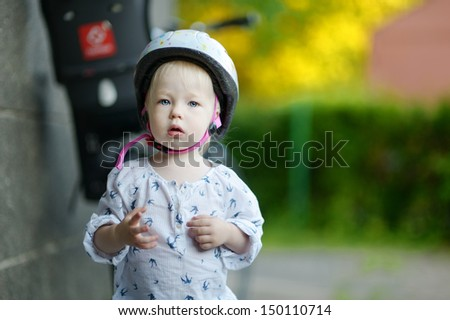 Little toddler girl ready to ride a bicycle
