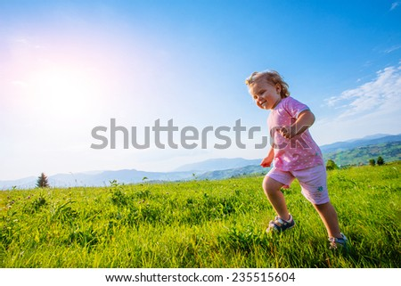 Little toddler girl running in a beautiful field between mountains  - stock photo