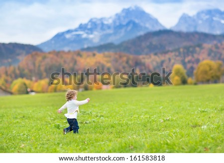 Little toddler girl running in a beautiful field between snow covered mountains - stock photo