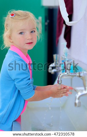 Little toddler girl washing her hands in the bathroom at school or kindergarten