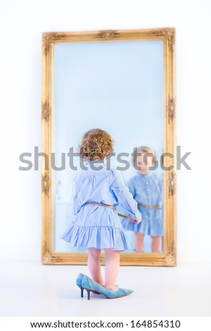 Little toddler girl with beautiful curly hair wearing a blue dress standing in front of a big mirror trying on her mother's high heels shoes - stock photo