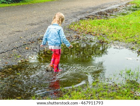 Little toddler girl with blonde pigtails en red boots splashing in the puddle. By playing in this way she discovers the world gradually.