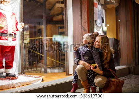 Little toddler girl with mother on Christmas market. Funny happy kid making window shopping with  Santa Claus. holidays, christmas, childhood and people concept - stock photo