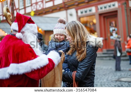 Little toddler girl with mother on Christmas market. Funny happy kid taking gift from bag of Santa Claus. holidays, christmas, childhood and people concept - stock photo