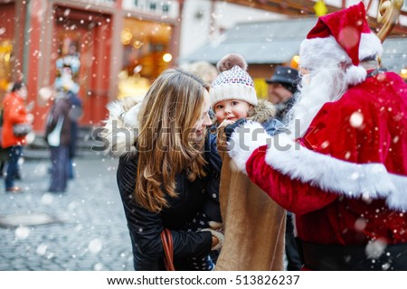 Little toddler girl with mother on German Christmas market. Happy kid taking gift from bag of Santa Claus. Xmas, childhood concept. Smiling woman and daughter, family celebrating traditional holiday.