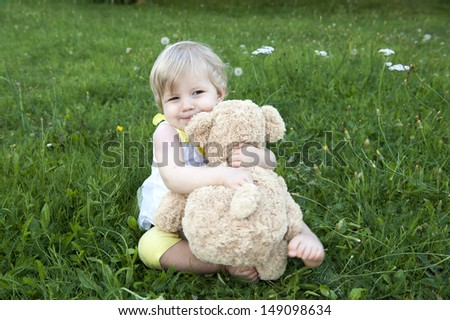 little toddler hugging her teddy bear, seated outdoors in the garden - stock photo