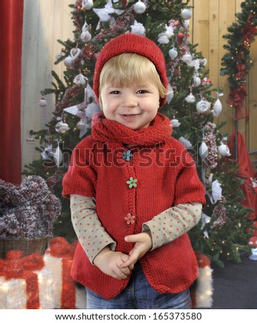 little toddler in red in front of a christmas tree