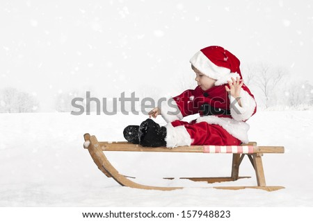 little toddler in santa claus outfit on a sledge outdoors in the snow