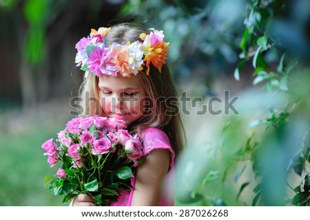 Little toddler lovely girl with flowers in pink dress at beautiful garden - stock photo