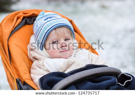 Little  toddler one year old in warm winter clothes and orange pram outdoor